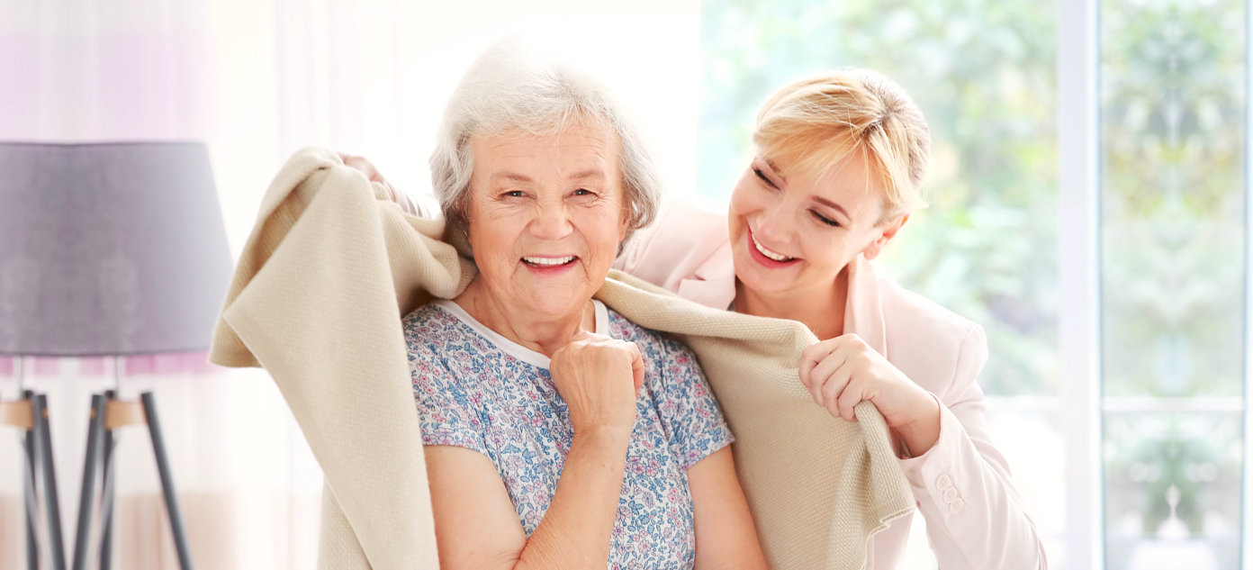 caregiver putting a blanket on a patient
