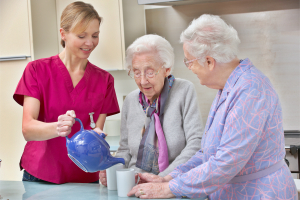 care giver pouring tea for the two elderly women