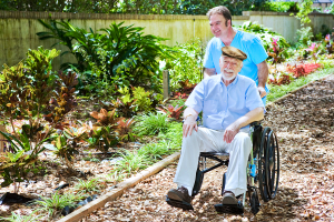 disabled senior man being pushed through a lovely garden by his nurse